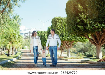 Happy caucasian family couple with little kid walking on park alley. - stock photo