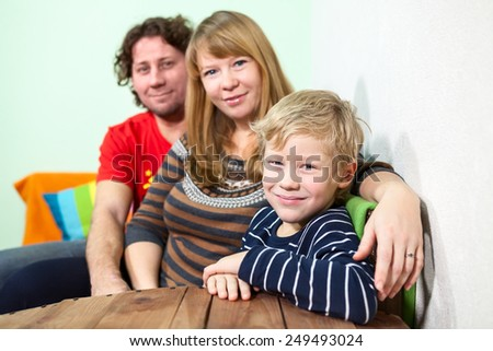 Happy Caucasian family of three people sitting in the room - stock photo