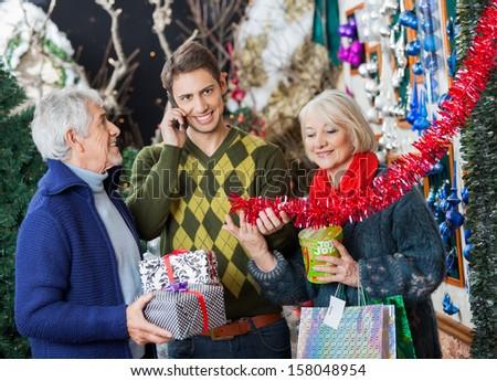 Happy Caucasian family of three shopping in Christmas store - stock photo