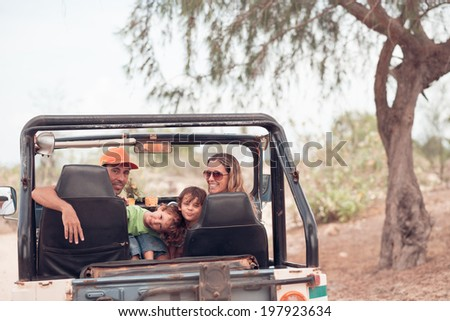 Happy Caucasian family sitting in the off-road vehicle - stock photo