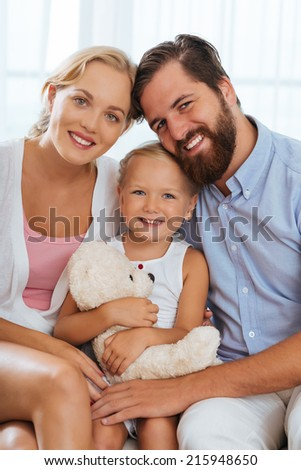 Happy Caucasian family smiling and looking at the camera - stock photo