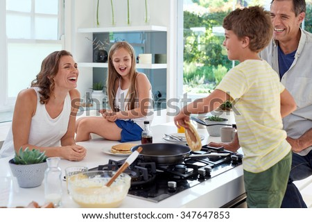 Happy caucasian family standing around stove, son making pancakes on stove