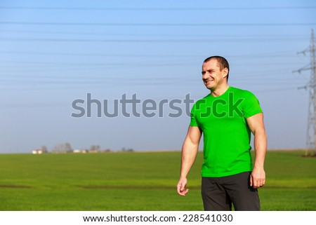 Happy caucasian farmer standing in a meadow, with copy-space on the clear sky  - stock photo