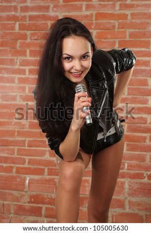 Happy Caucasian female with a microphone singing against a brick wall - stock photo