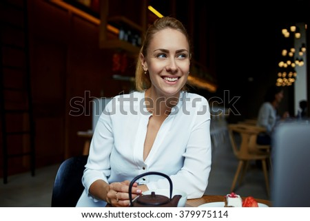 Happy Caucasian female with cute smile dreaming about something good while sitting in comfortable cafe during free time, cheerful woman looking away while relaxing in cozy coffee shop after walking - stock photo
