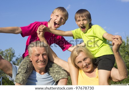 Happy Caucasian fortune grandparents with grandchildren with fool on the street - stock photo