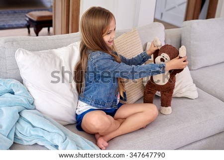 Happy Caucasian girl playing with brown teddy bear at home sitting on couch in living room