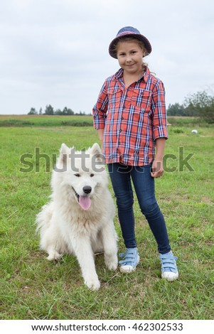 Happy Caucasian girl standing on green grass with sitting beside white dog