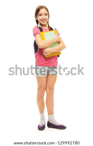 Happy Caucasian girl with books and beautiful ponytails standing holding pile of books and smiling, isolated on white, full length portrait - stock photo