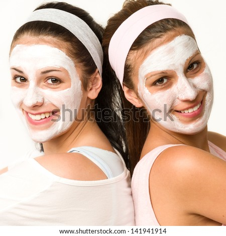 Happy caucasian girls with white facial mask - stock photo