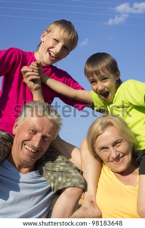 Happy Caucasian luck grandparents with grandchildren with fool on the street