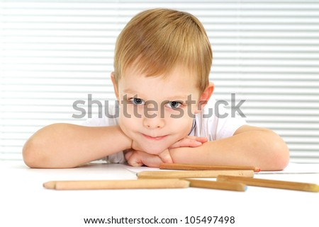 Happy Caucasian male sitting at the table draws on a light background - stock photo