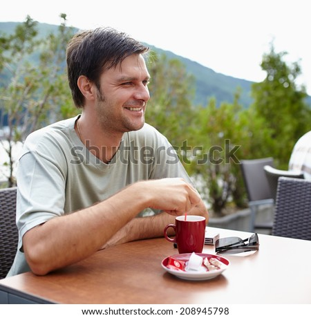 Happy caucasian man having a coffee outdoor on a terrace