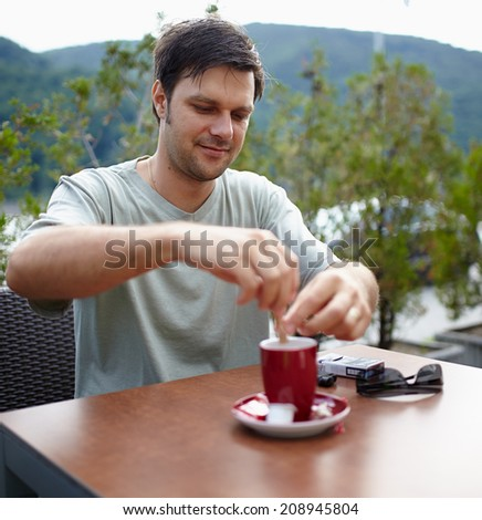 Happy caucasian man having a coffee outdoor on a terrace - stock photo