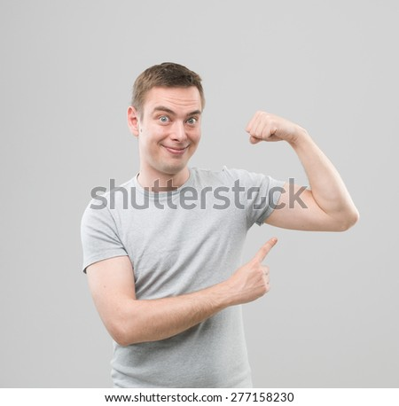 happy caucasian man pointing at his arm muscles and smiling, on grey background - stock photo