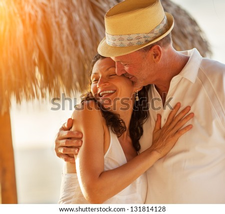Happy Caucasian mature senior adult couple kiss on tropical beach, closeup. - stock photo