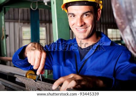 happy caucasian mechanic repairing heavy industry machine - stock photo