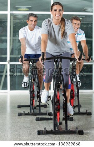 Happy Caucasian men and woman on exercise bikes in health club - stock photo