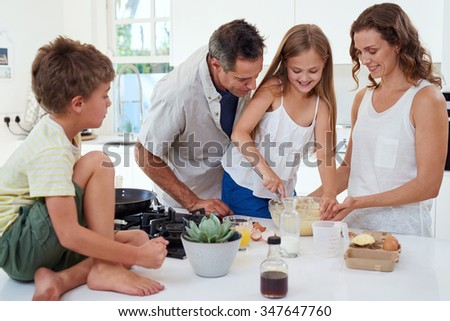 Happy caucasian smiling family baking together in the kitchen - stock photo