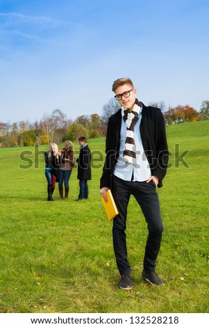 Happy Caucasian student in the park with friends standing with book and wearing glasses