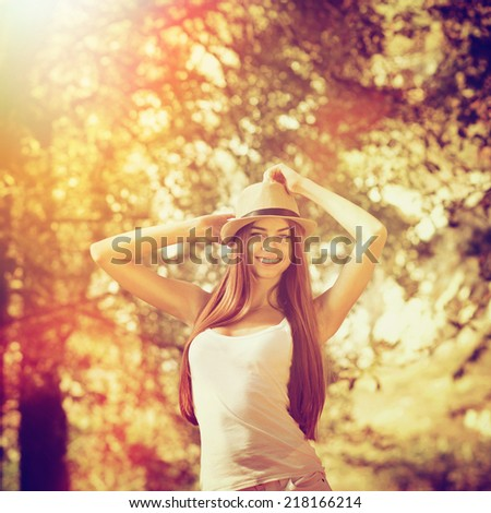 Happy Caucasian teenage girl with hat wearing white shirt posing outdoors in autumn. Young woman having fun posing and smiling in park on sunny fall day. Instagram filter look. - stock photo