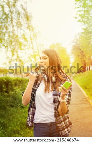 Happy Caucasian teenage girl with smartphone in park. Beautiful fun young woman with smart phone laughing outdoors on sunny summer day. Candid shot.  - stock photo