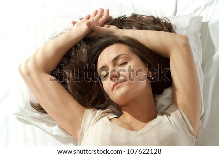 Happy Caucasian woman lying on a pillow on a light background - stock photo