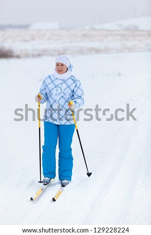 Happy Caucasian woman skiing in wintry field alone - stock photo