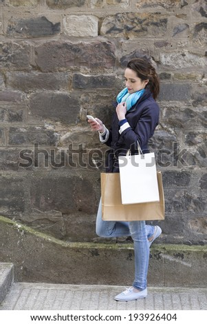 Happy Caucasian woman using a smartphone and holding shopping bags by stone wall. Lifsetyle image shot in United Kingdom.  - stock photo