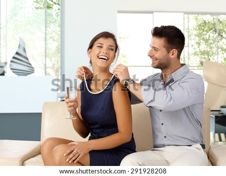 Happy caucasian woman with champagne in hand getting pearl necklace gift from husband. Happy couple, sitting at home on sofa in living room, romance, jewelry. - stock photo