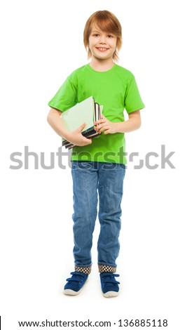 Happy Caucasian 9 years old boy in green shirt holding pile of books, full height portrait, isolated on white - stock photo