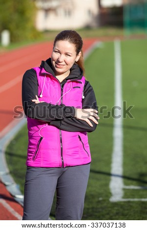 Happy Caucasian young woman portrait with clasped hands, standing at the stadium in sport clothes  - stock photo