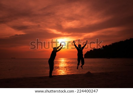 happy celebrating winning success people jumping holding sun silhouette