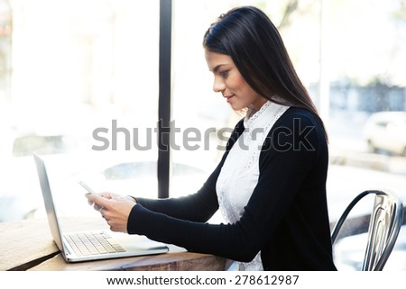 Happy charming businesswoman using smartphone in cafe
