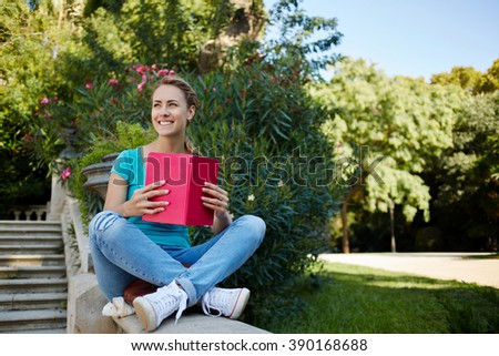 Happy charming hipster girl is looking for someone while is sitting with notebook in beautiful park in spring day, smiling female with good mood is enjoying her interesting book and recreation time - stock photo
