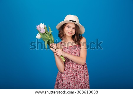 Happy charming little girl standing and holding bouquet of tulips over blue background - stock photo