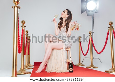 Happy charming woman holding heels and glass of champagne on red carpet - stock photo