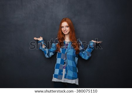 Happy charming young woman holding copyspace on two palms over blackboard background - stock photo