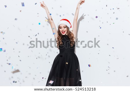 Happy charming young woman in santa claus hat standing with raised hands over white background