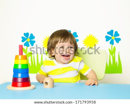 Happy cheerful baby at kindergarten or playgroup, Child playing with pyramid toy at home, happy education concept, colorful, studio shot.  - stock photo