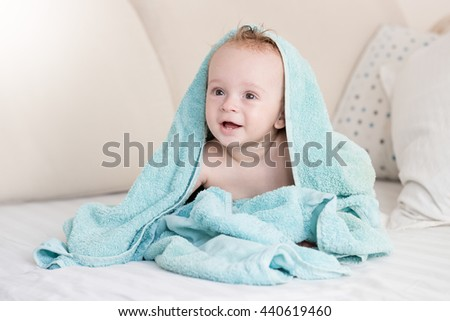 Happy cheerful baby boy sitting on bed under blue blanket - stock photo