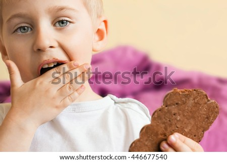 Happy cheerful boy eating chocolate keeps rukazh chocolate bar, chocolate smeared,   Selective focus - stock photo