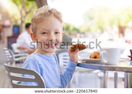 happy cheerful boy enjoying cookie in outdoor cafe - stock photo