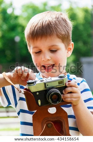 Happy cheerful boy with a camera, the baby photographed outdoors, soft focus - stock photo