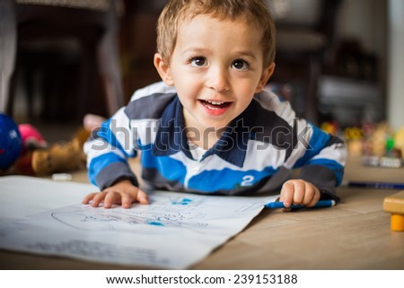 Happy cheerful child drawing at home. Creativity concept - stock photo