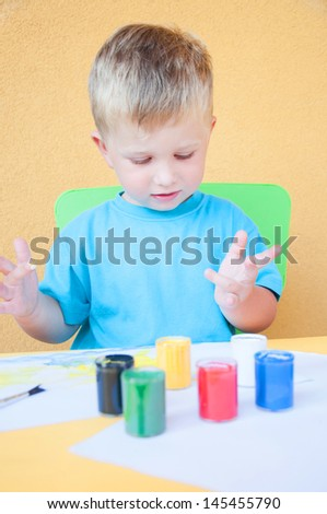 Happy cheerful child drawing with brush. - stock photo