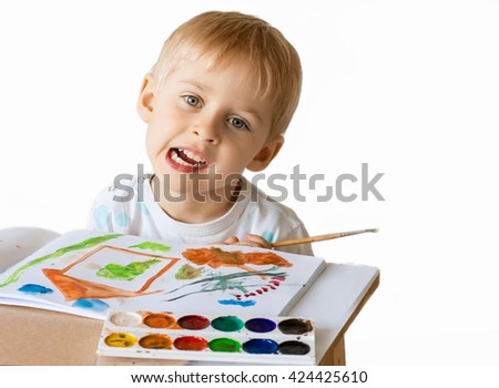 Happy cheerful child draws paints in an album, using a variety of drawing tools. Creativity concept boy holding a brush, a happy childhood - stock photo