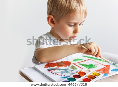 Happy cheerful child draws paints in an album, using a variety of drawing tools. Creativity concept of a boy holding a brush, a happy childhood,   Selective focus - stock photo