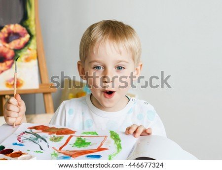 Happy cheerful child paint with brush in album using a lot of tools for drawing. Creativity concept boy draws paints and holds a brush, a happy childhood   Selective focus - stock photo