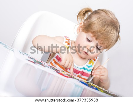 Happy cheerful child painting with paintbrush and colors. Kid creative activities concept.